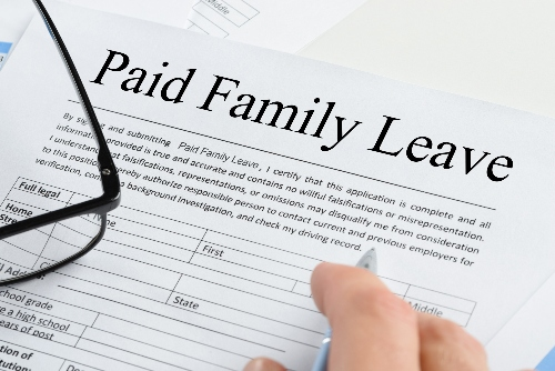 A document that reads Paid Family Leave rests on a desk.