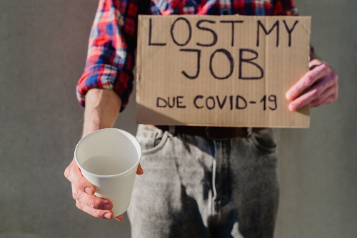 A man holds a cup for change and a sign that reads