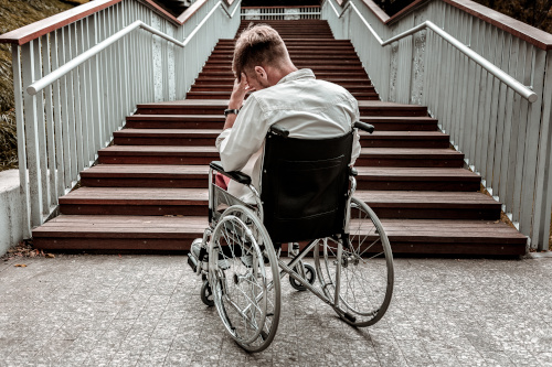 A man in a wheelchair puts his head in his hand at the bottom of a flight of stairs.